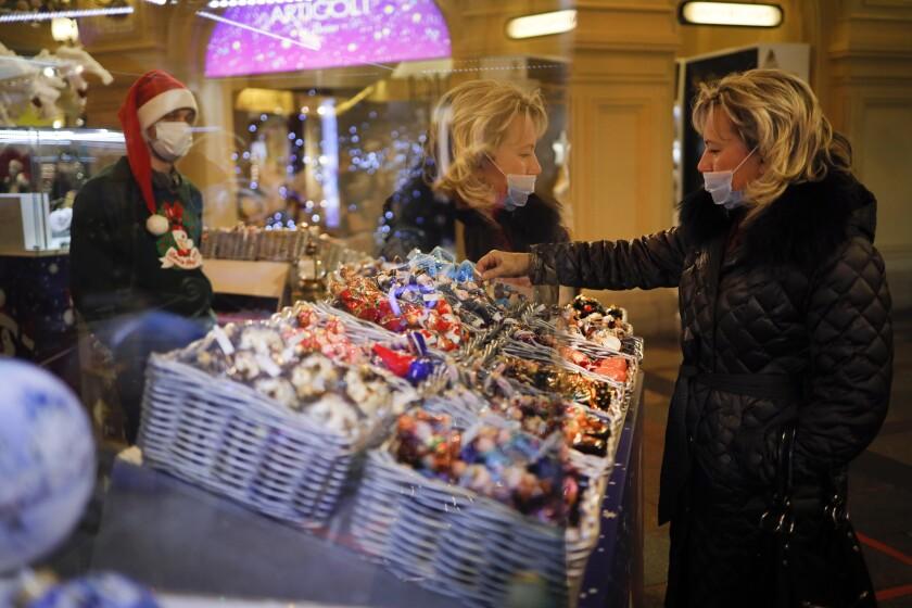 Una mujer con una mascarilla protectora contra el coronavirus examina adornos navideños