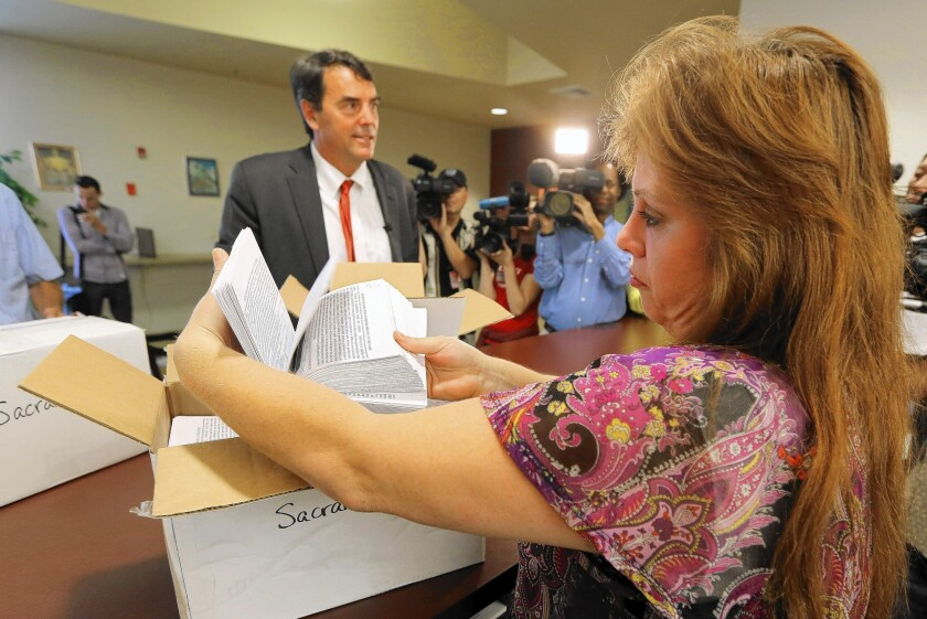 Sacramento County elections official Heather Ditty collects petitions turned in by Silicon Valley venture capitalist Tim Draper, who is backing a plan to split California into six states.