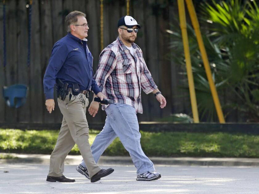 George Zimmerman, right, is escorted to a home by a police officer Monday in Lake Mary, Fla., after a domestic incident involving his wife, Shellie.