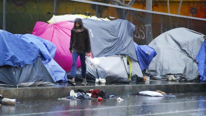 A pedersterian walks along Island Avenue near homeless tents between 17th and 19th streets in East V