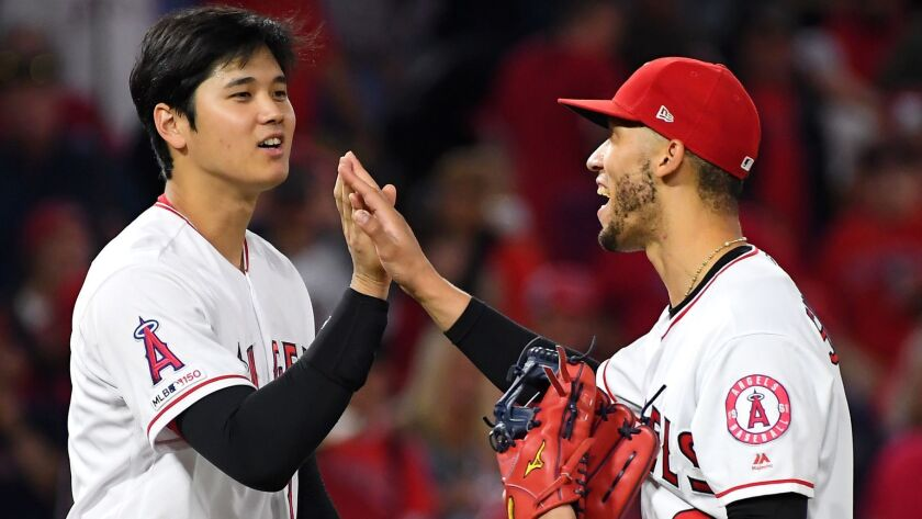 Angels' Shohei Ohtani, left, gives a high five to Andrelton Simmons after the final out against the Oakland Athletics at Angel Stadium on Thursday.