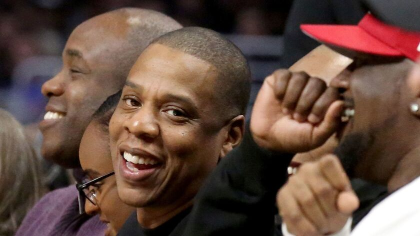 Rapper Jay Z, center, at a Clippers-Warriors game in Los Angeles, will continue his long-standing partnership with Live Nation.