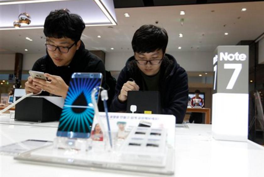 Dos jóvenes revisan teléfonos Galaxy Note 7 de Samsung Electronics en una tienda de la empresa coreana en Seúl, Corea del Sur, el 10 de octubre de 2016. Samsung pidió apagar y dejar de usar sus teléfonos Note 7, que son propensos a incendiarse, dejando a muchos usuarios sin una herramienta de la que dependen cada vez más. (AP Foto/Ahn Young-joon, File)