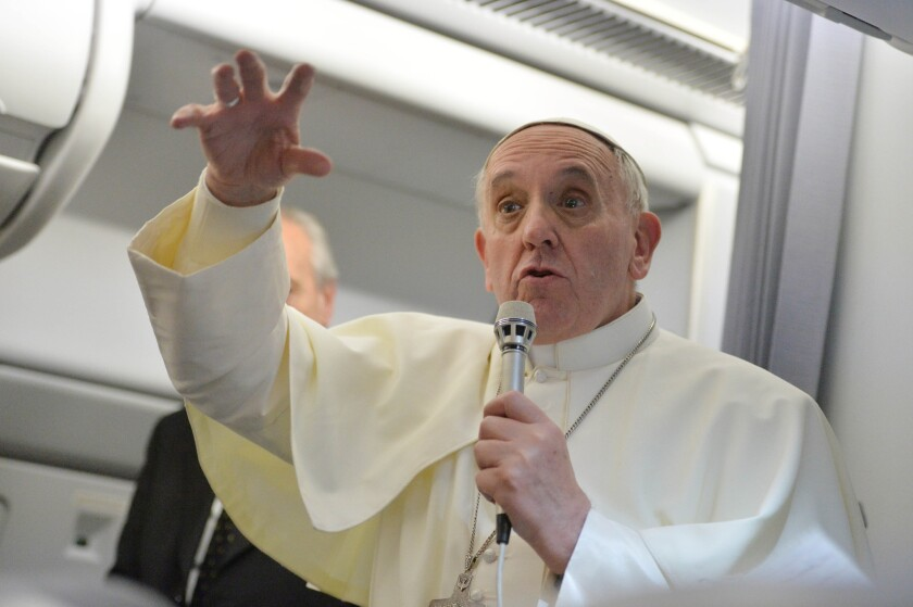 Pope Francis answers questions during a news conference aboard the papal flight on the journey back from Brazil on Monday.