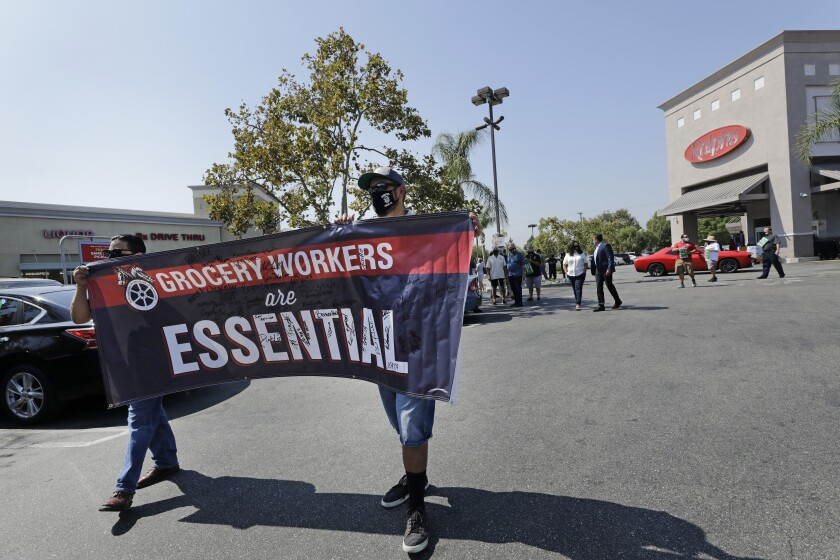 """Two people hold up a banner that reads """"Grocery Workers are Essential"""""""