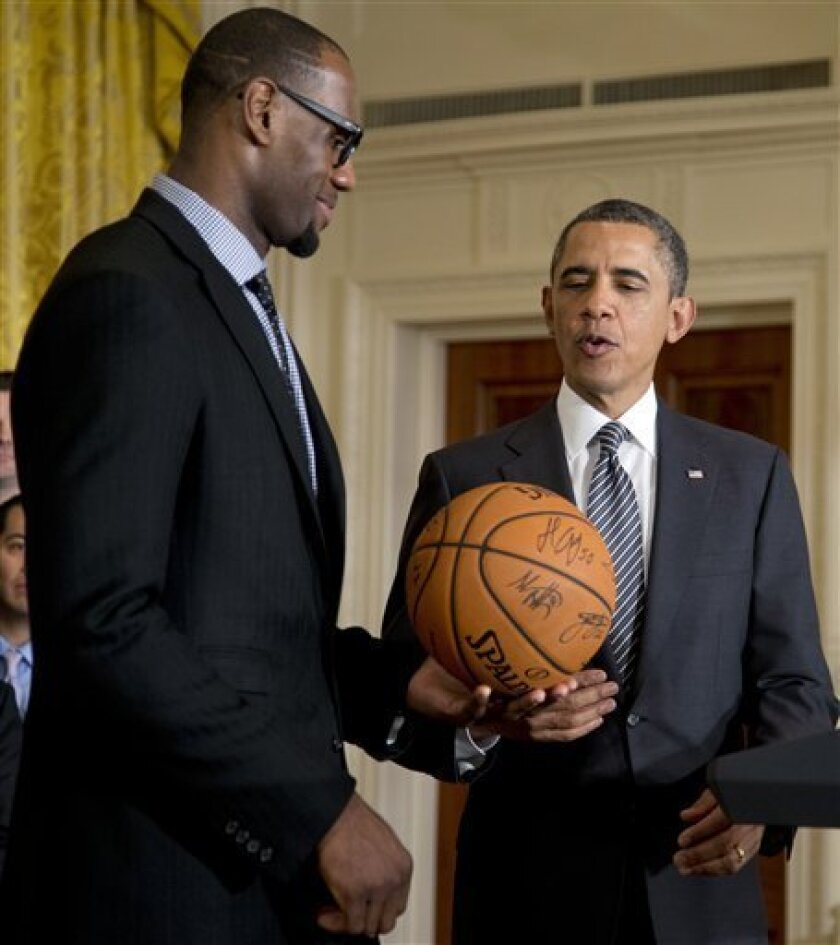 President Barack Obama accepts a signed basketball from Miami Heat forward LeBron James as he welcomes the the NBA basketball champion Miami Heat, to the East Room of the White House, Monday, Jan. 28, 2013, in Washington. (AP Photo/Carolyn Kaster)
