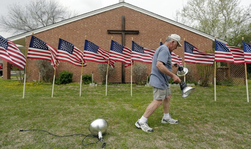 Bob Gordon works on a memorial April 3, 2014, at Central Christian Church in Killeen, Texas, one day after a soldier opened fire on fellow service members at Fort Hood military base. The gunman killed three people and wounded 16 before committing suicide. (AP Photo/Eric Gay)