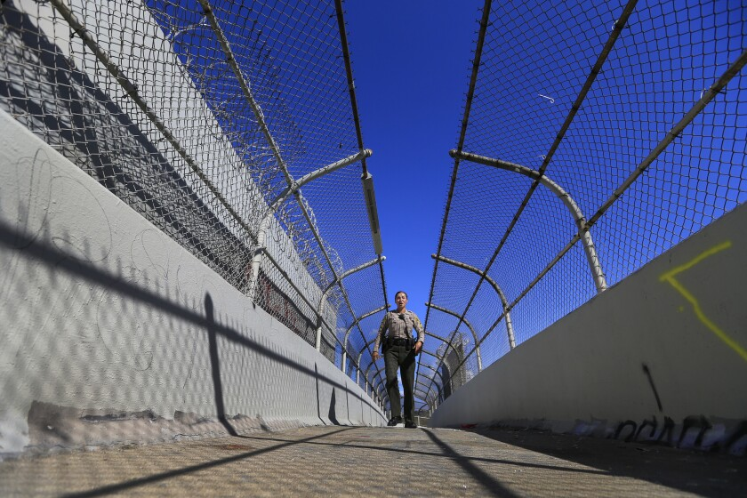 Los Angeles County Sheriff's Deputy Joanne Arcos, who works with many Proposition 47 offenders, walks across a pedestrian overpass to check in on repeat offenders in an unincorporated area in Hacienda Heights.