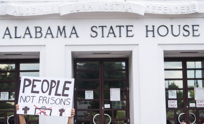 People protest the prison plan outside the Alabama State House in Montgomery, Ala., on Wednesday, Sept. 29, 2021. Alabama lawmakers have begun began debate on a prison construction package that would tap $400 million of the state's pandemic relief funds to help pay for building three new lockups. The Alabama House of Representatives is expected to vote on the bills Wednesday evening. (Jake Crandall /The Montgomery Advertiser via AP)