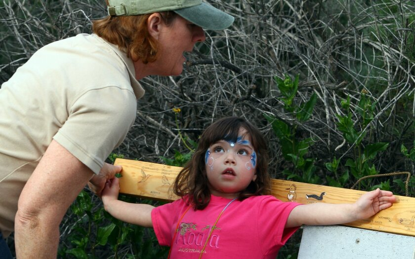 Bella Masanis, 3, is told by San Elijo Lagoon Conservancy volunteer that she has a wingspan of a mallard duck, depicted on a bench at the San Elijo  Lagoon Ecological Reserve.