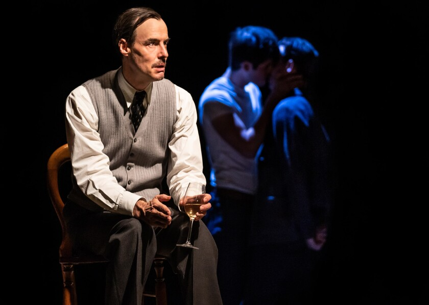 """Paul Hilton, in a chair with a glass of white wine, plays E.M. Forster in """"The Inheritance."""" Behind him in shadow are two men kissing."""