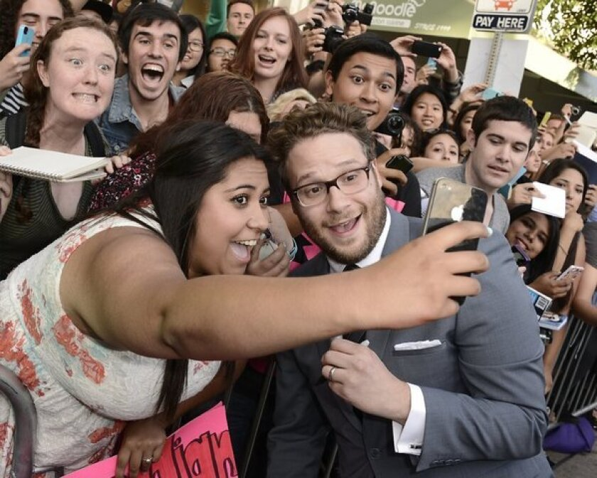 """A fan takes a picture with Seth Rogen at the premiere for """"This Is the End"""" in Westwood."""