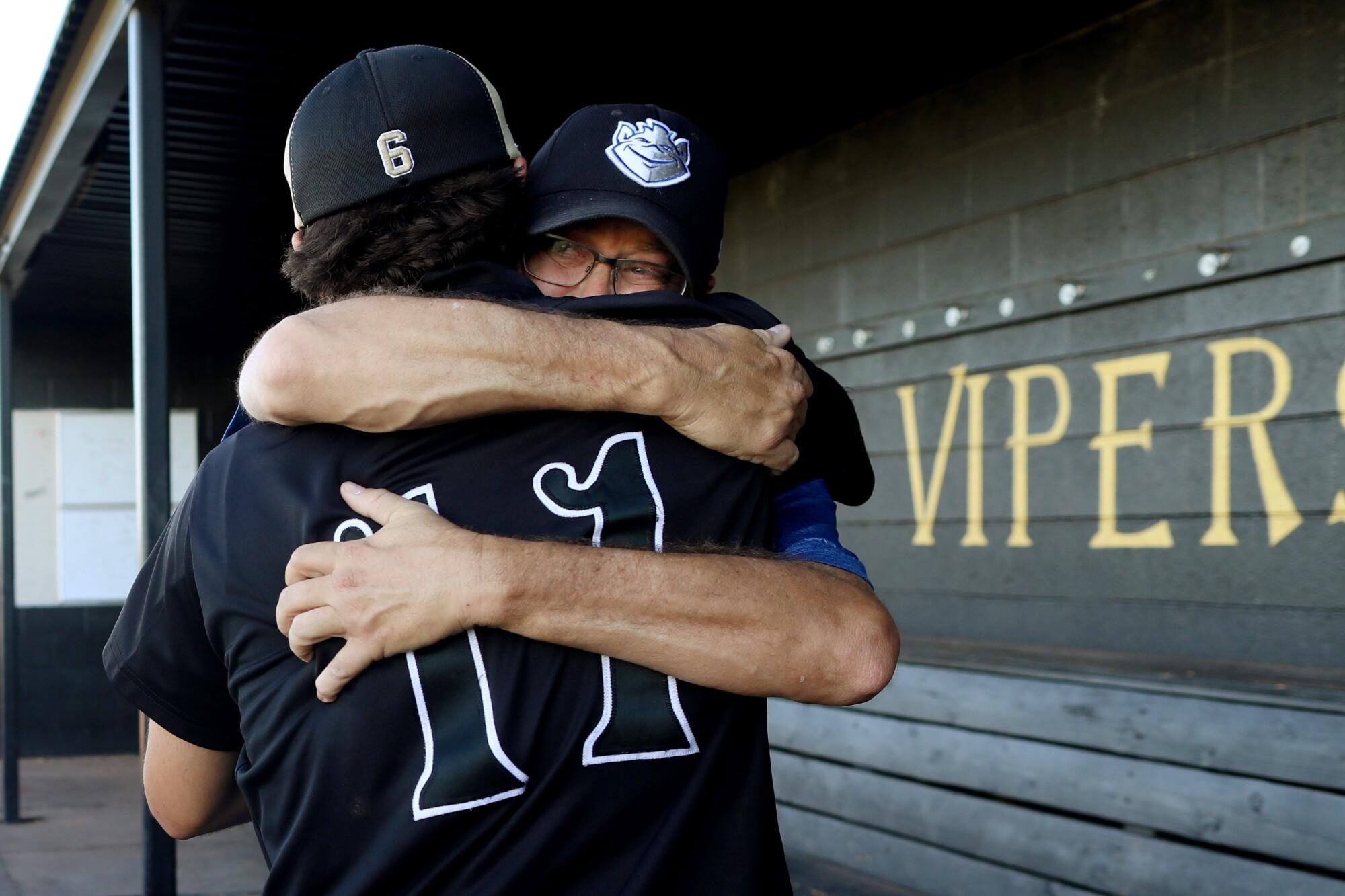 Tanner Spallina, a catcher on the Verrado High School baseball team, hugs Daryl McKinsey at the school in Buckeye, Ariz.