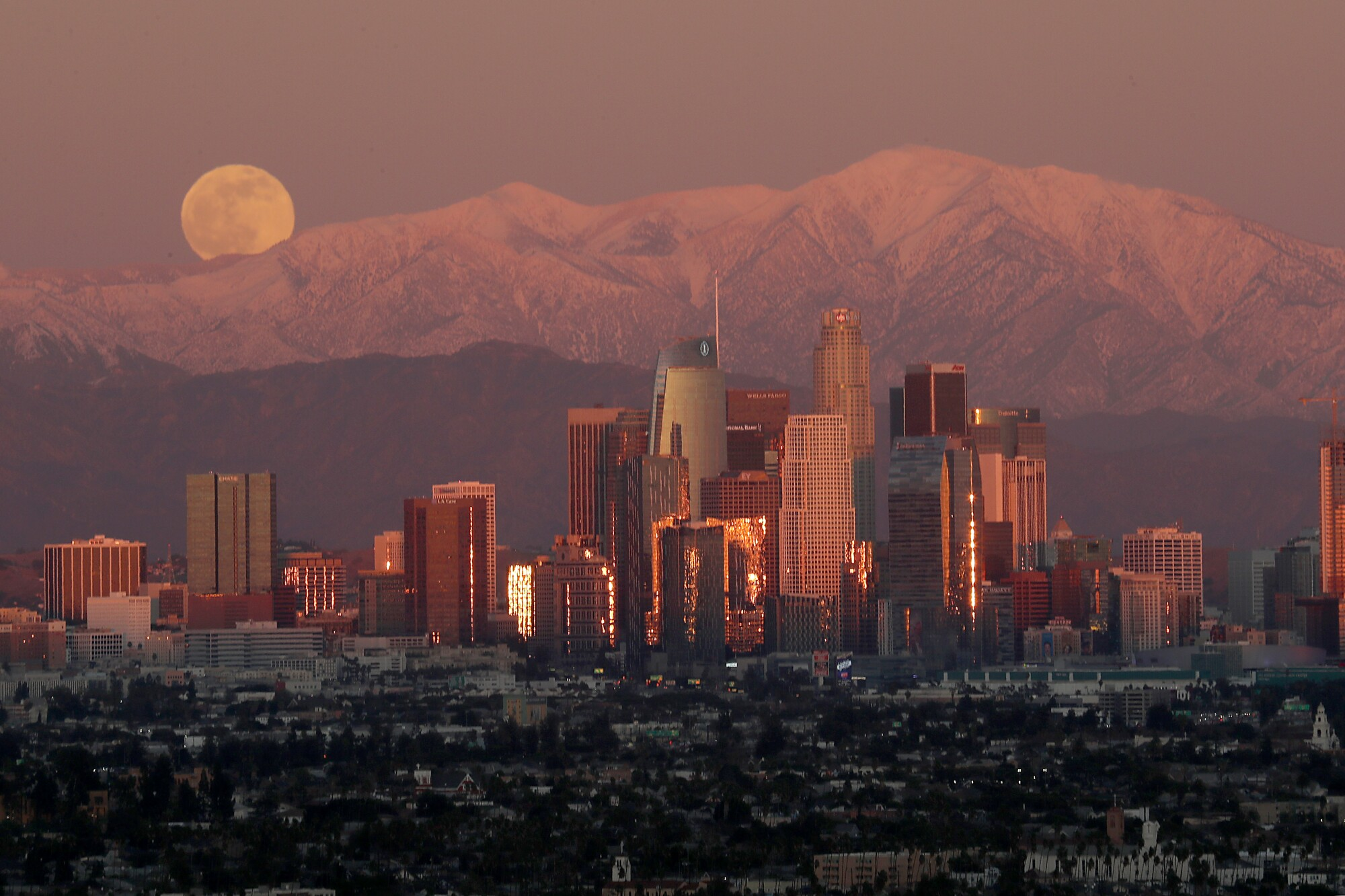 A full moon rises over the snow-capped San Gabriel Mountains and the skyline of downtown Los Angeles.