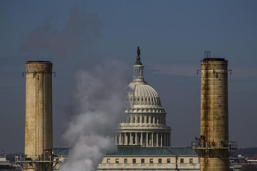 Vista del domo del Capitolio entre dos chimeneas de la Planta de Energía Capital, la única central eléctrica de carbón en la capital de Estados Unidos, en Washington. EFE/Archivo