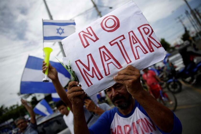 """Un hombre muestra una pancarta mientras cientos de nicaragüenses participan en la caravana """"Nicaragua no olvida, Nicaragua no se rinde"""" por barrios populares de Managua (Nicaragua). EFE/Archivo"""