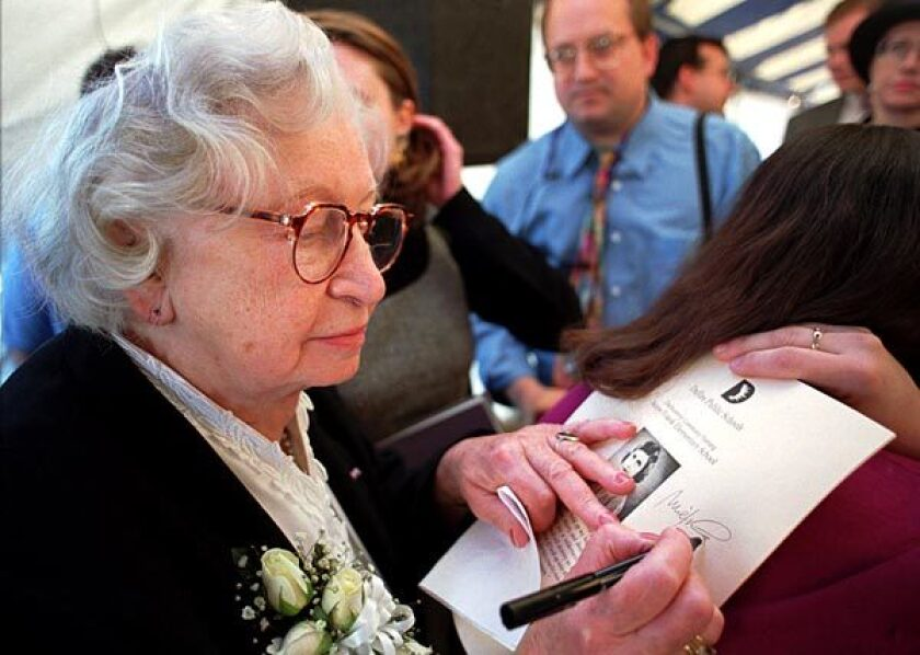 Miep Gies signs a program at the dedication ceremony for Anne Frank Elementary School in Dallas on Nov. 14, 1995.