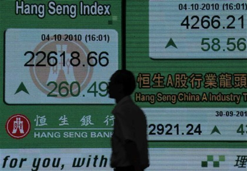 A man walks past the electronic stock board of a local bank in Hong Kong Monday, Oct. 4, 2010 in Hong Kong. Hang Seng index jumped 1.2 percent to 22,618.66, with particular strength seen in the property sector. (AP Photo/Vincent Yu)