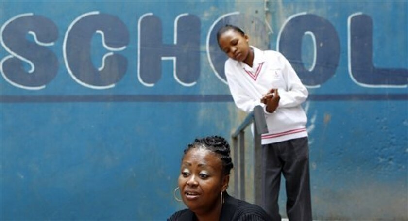 In this Oct. 28, 2010 photo, Dintle Zulu, foreground, speaks during an interview, as her daughter Samantha, looks on at the Progressive Primary in Johannesburg. Progressive Primary is among an increasing number of such schools for poor South Africans underserved by a government that has struggled t