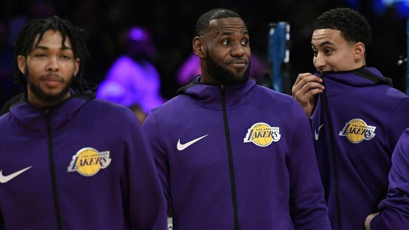 Lakers' LeBron James, flanked by Brandon Ingram, left, and Kyle Kuzma, remains sidelined.