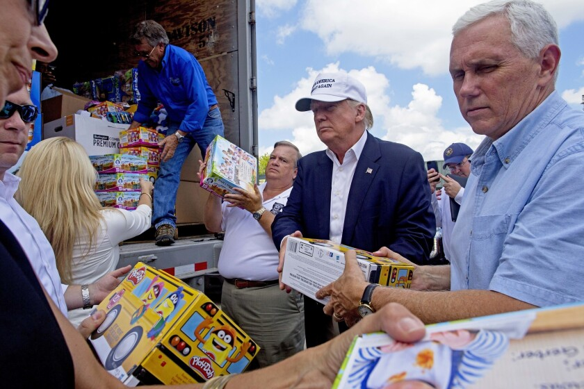 Republican presidential candidate Donald Trump and his running mate, Indiana Gov. Mike Pence, right, help to unload supplies for flood victims during a tour of the flood damaged area in Gonzales, La., on Friday.