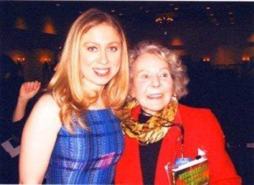Doris McCoy (right) meets Chelsea Clinton, and gives the first copy of her book, 'Remarkable Leaders: Risk Takers Who Dare Us,' to former President Bill Clinton.