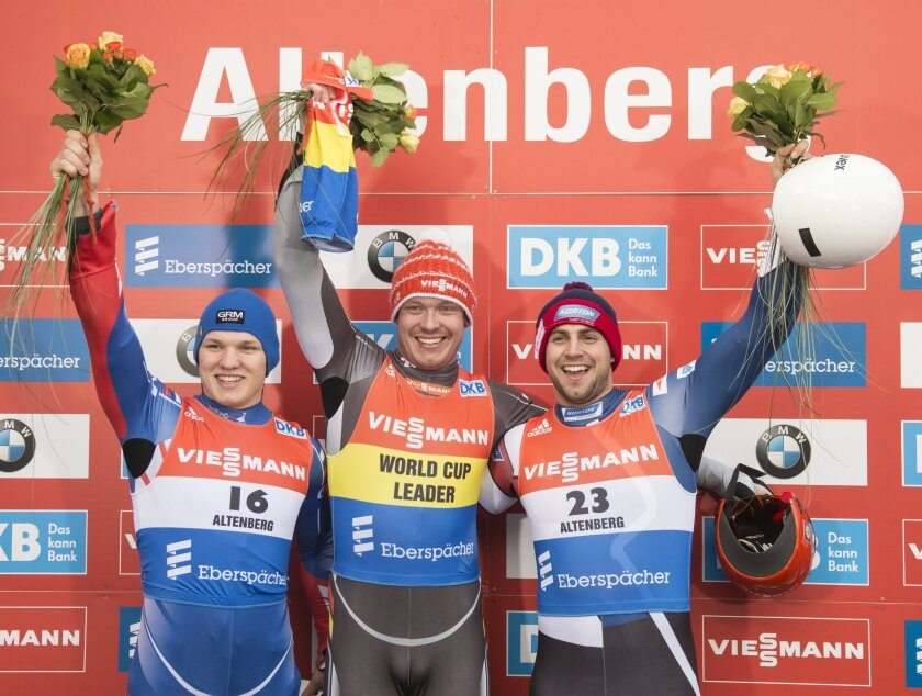Winner Felix Loch of Germany, center, celebrates besides the second placed Roman Repilov of Russia, left, and the third placed Chris Mazdzer of USA, right, during the flower ceremony at the men's  luge World Cup race in Altenberg, eastern Germany, Saturday, Feb. 13, 2016. (AP Photo/Jens Meyer)