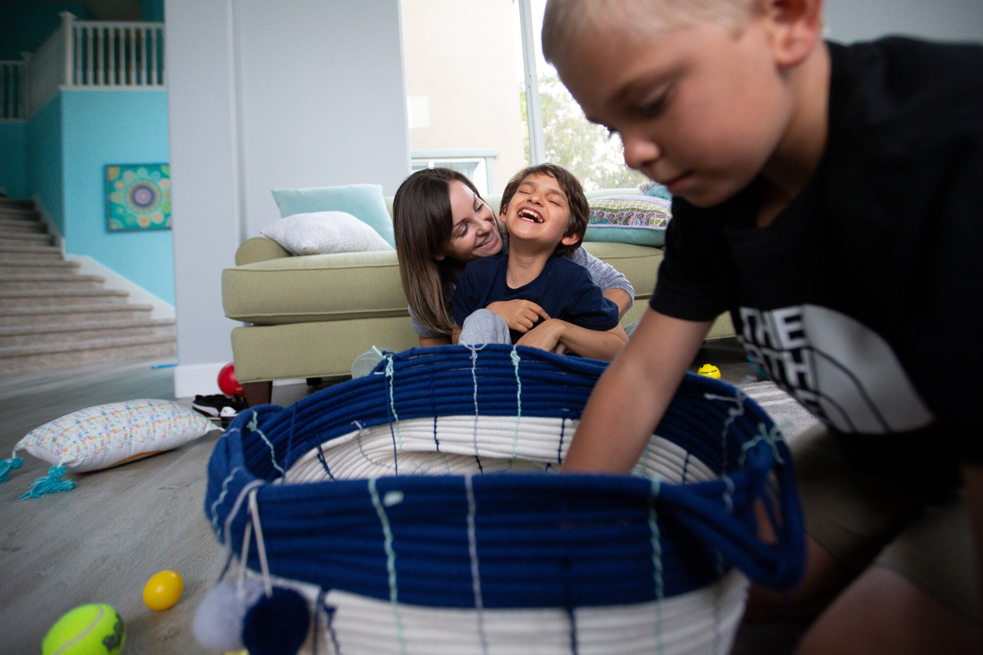 Kelley Dalby plays games with her sons Connor and Cameron in their home.
