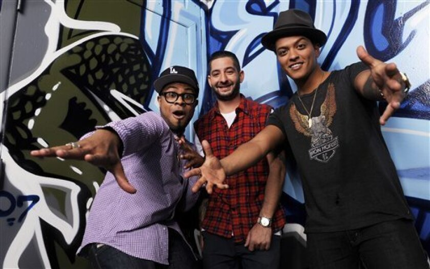 In this Jan. 4, 2012 photo, Philip Lawrence, left, Ari Levine, center, and Bruno Mars of the songwriting and production team The Smeezingtons, pose for a portrait at their recording studio in the Hollywood section of Los Angeles. Mars is nominated for six Grammy awards on Sunday, including best record, album and song of the year. (AP Photo/Chris Pizzello)