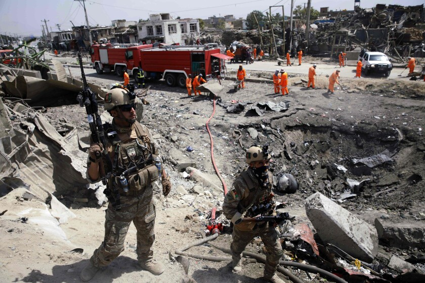 Afghan security forces pass near a crater from a Taliban bombing in Kabul on Sept. 3.