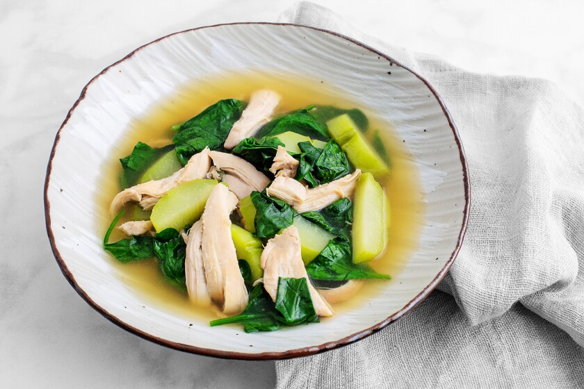 This soup has chicken poached in a ginger-, garlic- and onion-scented broth with chayote and baby spinach.
