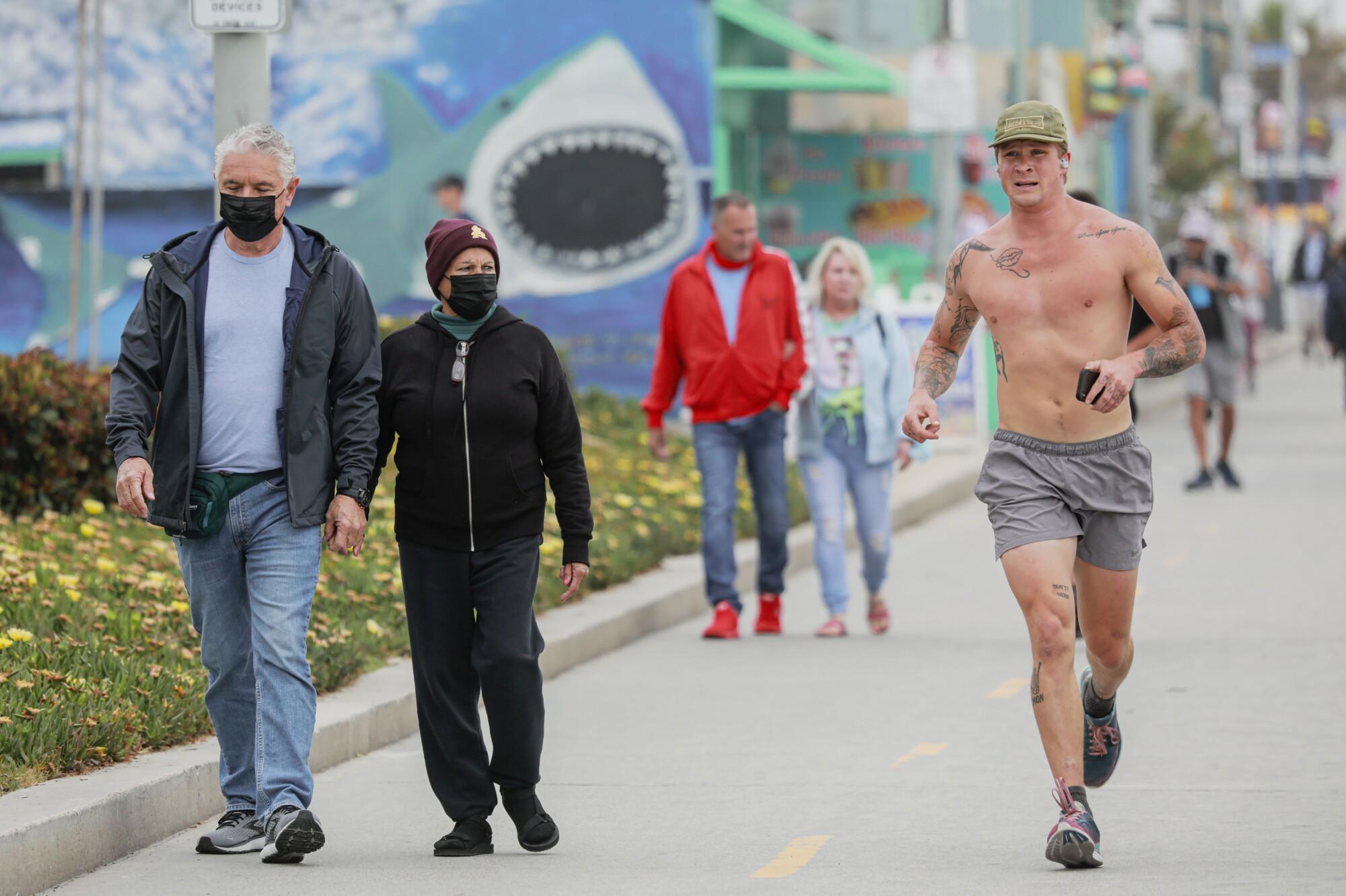 La gente camina por el paseo marítimo de Pacific Beach el mes pasado.