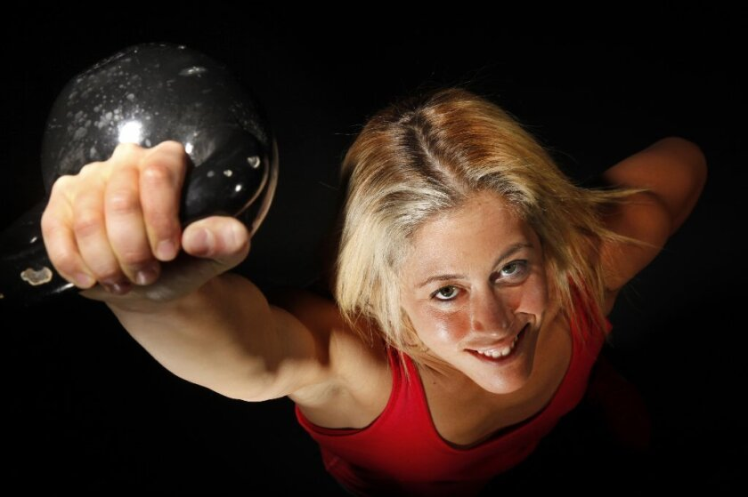 Fitness trainer Lacey Stone lifts a kettle bell.
