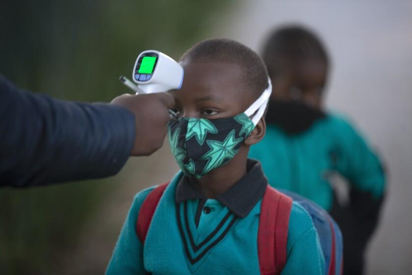 Un adulto comprueba la temperatura corporal de un alumno al regresar a la escuela en Johannesburgo, el martes 7 de julio de 2020, cuando se reabrieron más centros. Las escuelas habían cerrado en marzo en un intento de impedir contagios del nuevo coronavirus. (AP Foto/Denis Farrell)
