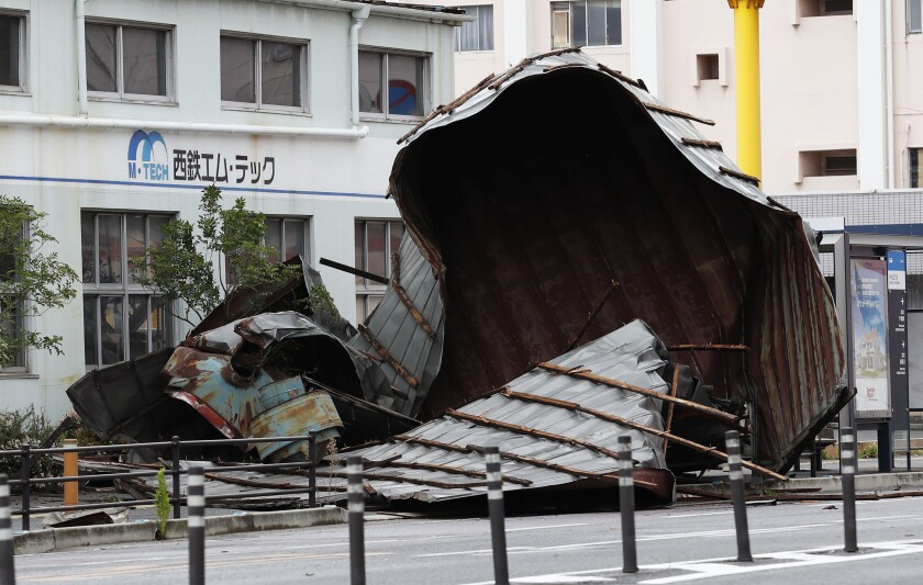 The roof of a car factory is left on sidewalk after typhoon hit Fukuoka, southwestern Japan Monday, Sept. 7, 2020. The second powerful typhoon to slam Japan in a week left people injured, damaged buildings, caused blackouts at nearly half a million homes and paralyzed traffic in southern Japanese islands before headed to South Korea.(Kyodo News via AP)