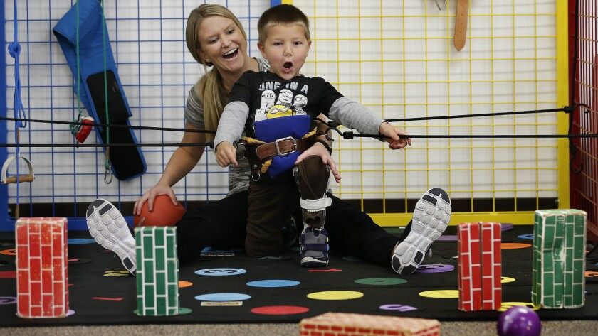 Physical trainer Kelsey Stewart reacts with Lucian Olivera as he successfully knocks over a fake brick with a ball during a session at the Simi Valley Hospital Child Development Center.