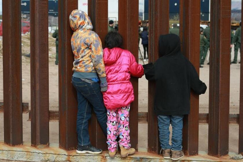 Un grupo de niños observan a agentes de migración de Estados Unidos que realizan practicas en las cercanías del muro fronterizo en la ciudad de Tijuana en el estado de Baja California (México). EFE/Archivo