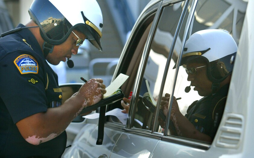 A Los Angeles World Airports police officer writes a citation to a motorist for running a red light at LAX.