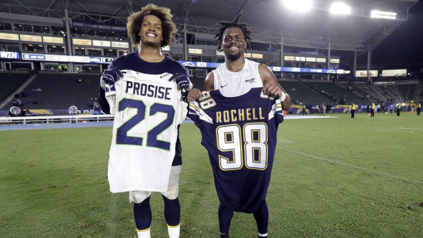 Chargers defensive end Isaac Rochell, left, swaps jerseys with Seattle Seahawks running back C.J. Prosise at the end of a preseason game on Saturday.