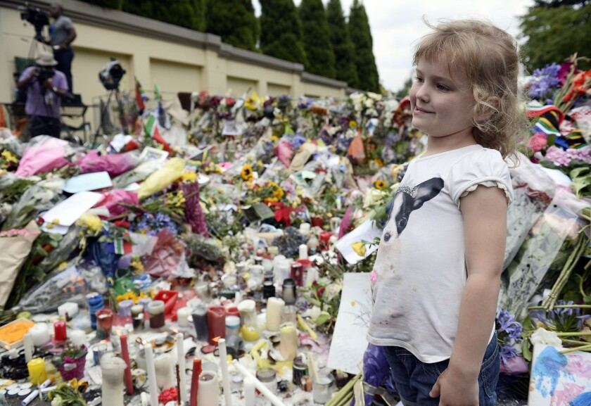 A child looks at flowers and tribute messages outside Nelson Mandela's home in Johannesburg, South Africa.