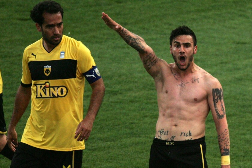 AEK Athens teammate Roger Guerreiro looks on as Giorgos Katidis appears to give a Nazi salute during his goal celebration Saturday.