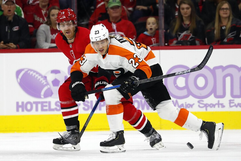 """File-Philadelphia Flyers' Oskar Lindblom (23) tries to clear the puck away from Carolina Hurricanes' Dougie Hamilton (19) during the second period of an NHL hockey game in Raleigh, N.C., Thursday, Nov. 21, 2019. Weeks after he completed bone cancer treatments, Lindblom returned to the Philadelphia Flyers to begin the unlikeliest of comebacks. Lindblom says he's """"happier than ever"""" to be back on the ice and skated with Flyers in Toronto Sunday, Aug. 16, 2020, before they played Montreal in Game 3 of the Eastern Conference playoffs. (AP Photo/Karl B DeBlaker, File)"""