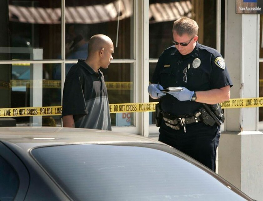 A San Diego Police officer interviews a witness outside the Chase Bank at 4627 College Avenue, at the corner of El Cajon Blvd., which was robbed before 10 a.m. June 7, 2010.