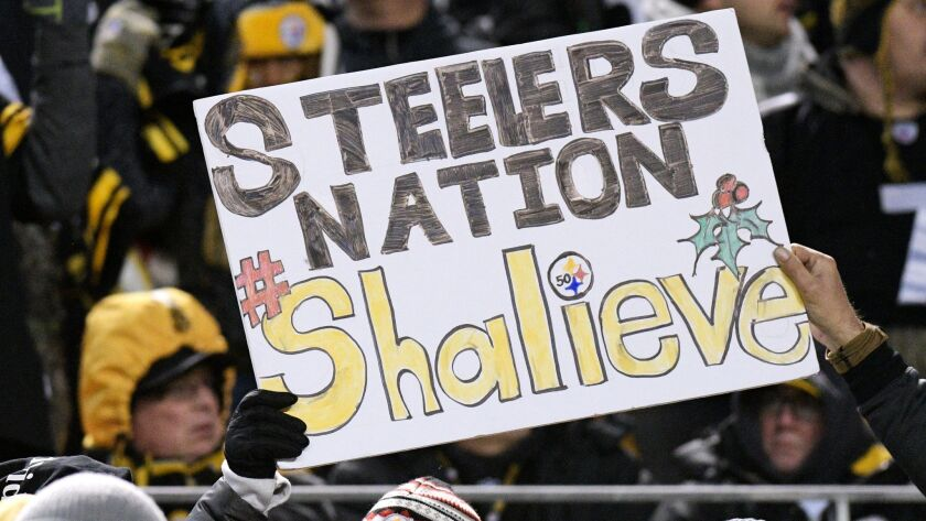 Pittsburgh Steelers fans hold a sign supporting injured Steelers linebacker Ryan Shazier.