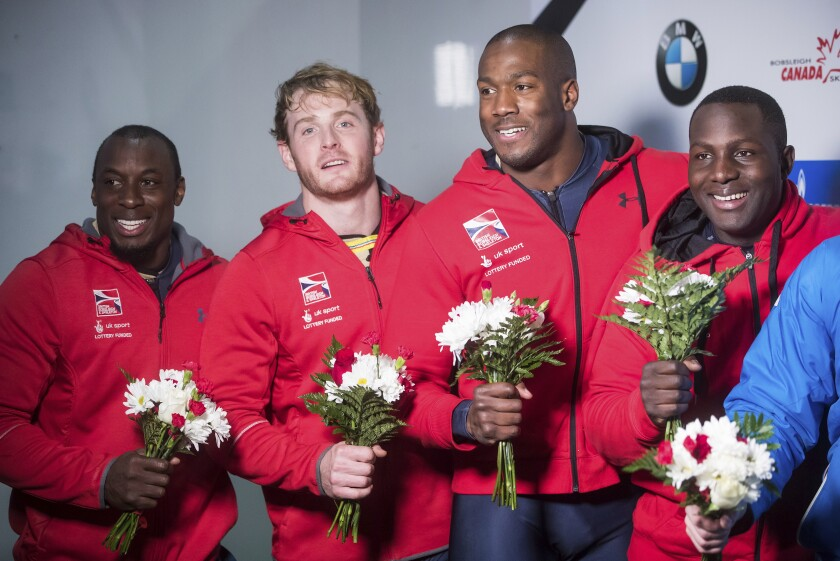 FILE - Great Britain's Andrew Matthews, from left to right, Ben Simons, Toby Olubi and Lamin Deen celebrate after their second-place finish in a four-man World Cup Bobsleigh race in Whistler, British Columbia, in this Saturday, Nov. 25, 2017, file photo. British Bobsleigh and Skeleton announced Thursday, June 17, 2021, that the four-man team of Deen, Simons, Olubi and Matthews has been upgraded to the gold medal for a race that occurred Nov. 25, 2017 in Whistler, Canada. The Russian crew that beat them that day has since been disqualified. (Darryl Dyck/The Canadian Press via AP, File)