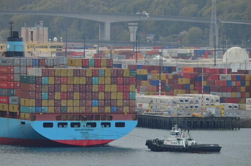 A tugboat pulls a cargo ship.