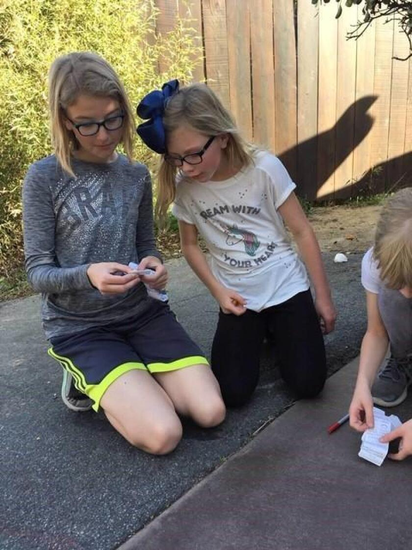 Girl Scouts Mercedes Howard from St. Charles Borromeo Academy and Ella Edson from Horizon Christian Academy read a geocache log to see who found the cache before them.