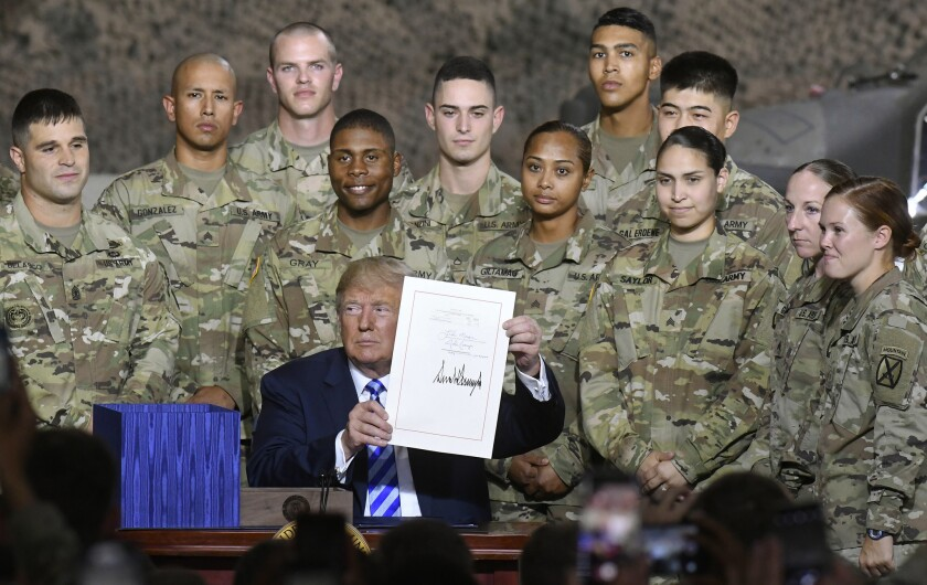 President Trump holds up the $716 billion defense policy bill named for Sen. John McCain that he signed during a ceremony in Fort Drum, New York, on Monday.