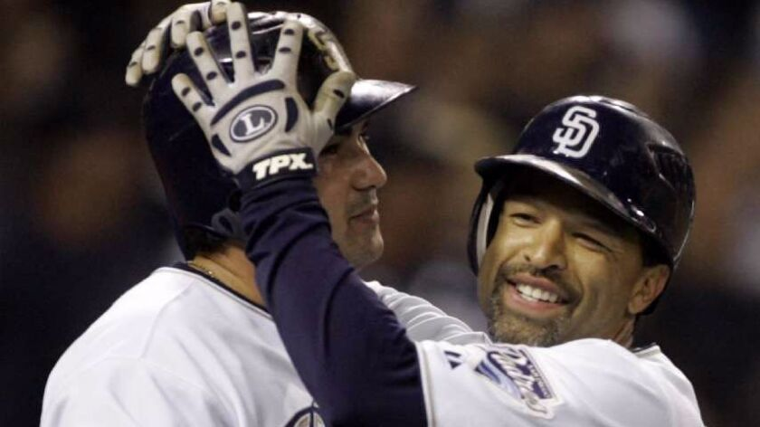 Padres outfielder Dave Roberts, right, hugs teammate Adrian Gonzalez after scoring a run on May 8, 2
