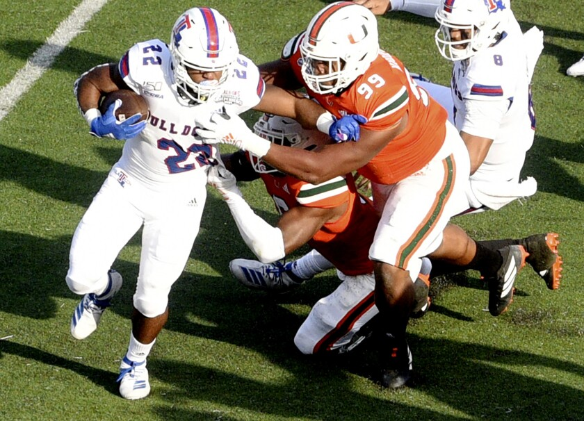 Louisiana Tech's Israel Tucker, left, runs with the ball during the game against Miami during the first half of the Independence Bowl on Thursday in Shreveport, La.